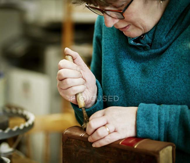 Femme travaillant sur la colonne vertébrale d'un livre relié — Photo de stock