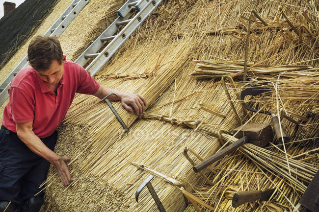 Man thatching a roof — Stock Photo