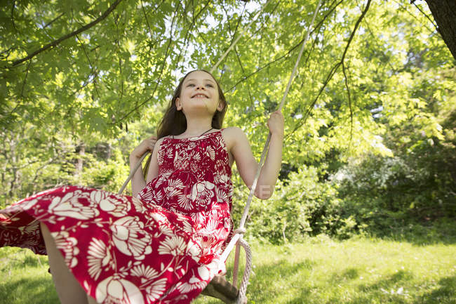 Girl on swing suspending from branches of tree — Stock Photo