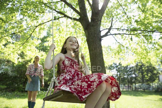 Дівчинка на гойдалках висить від Гілка дерева — стокове фото