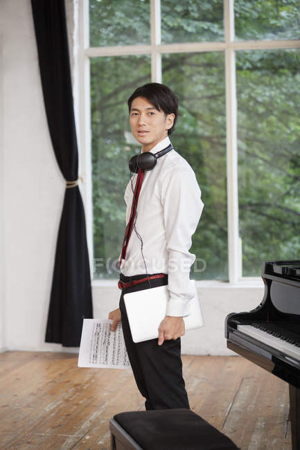 Man standing next to a grand piano — Stock Photo