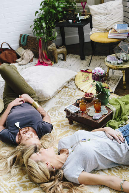 Women lying on floor with cushions and personal possessions — Stock Photo