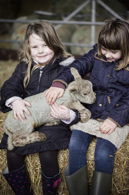 Little girls with newborn lamb — Stock Photo