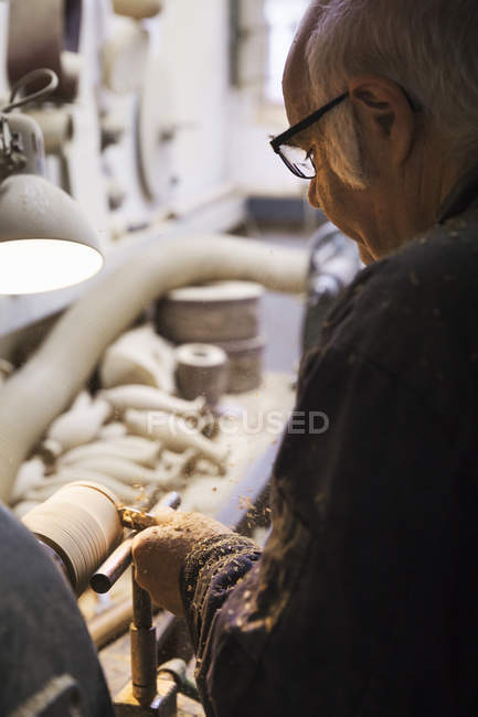 Man turning a piece of wood. — Stock Photo