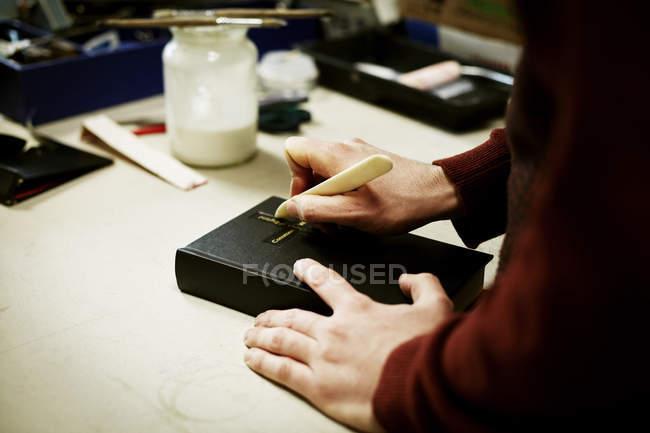 Homme utilisant l'outil de poche sur la couverture du livre — Photo de stock