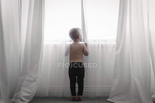 Kind schaut durch Netzvorhänge — Stockfoto