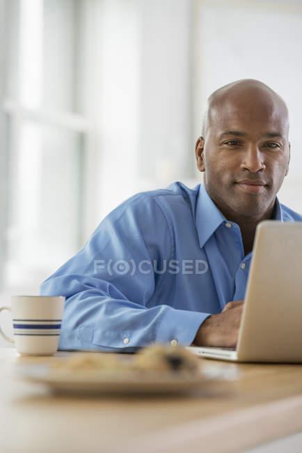 Businessman sitting using laptop — Stock Photo