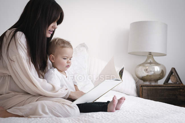 Pregnant woman reading with son — Stock Photo