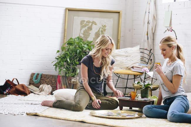 Mulheres sentadas no chão e jogando jogo — Fotografia de Stock