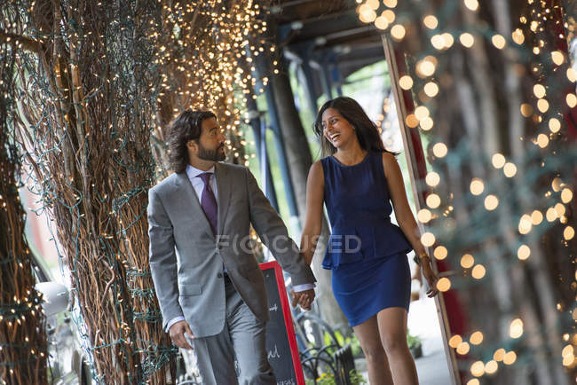 Couple walking under a pergola with lights. — Stock Photo