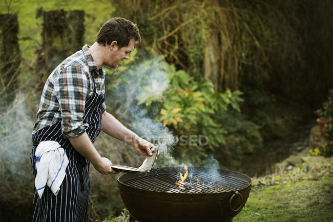 Chef grilling fish on a barbecue. — Stock Photo