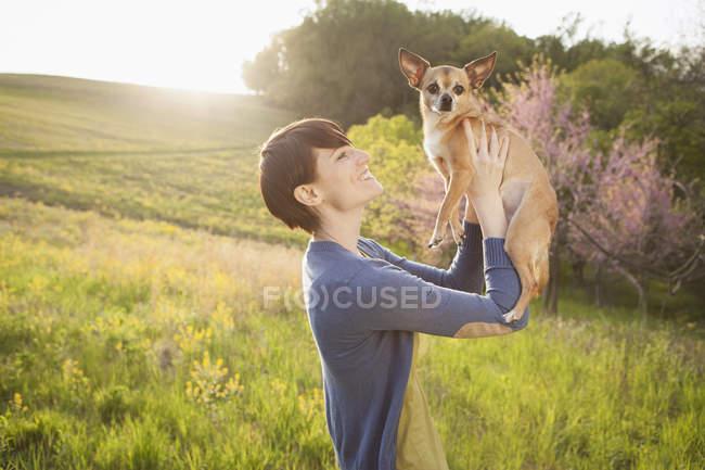 Femme tenant un petit chien chihuahua — Photo de stock