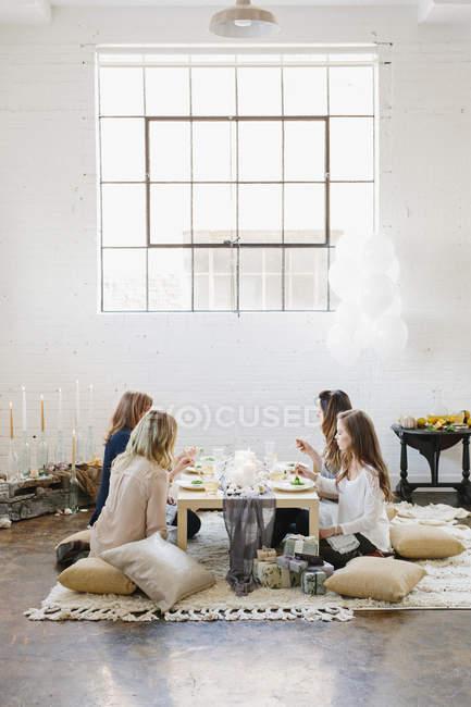 Жінки на низький столик на подушки. — стокове фото