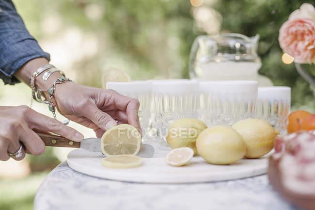 Donna affettare limoni per un drink . — Foto stock