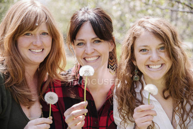 Women holding dandelions — Stock Photo