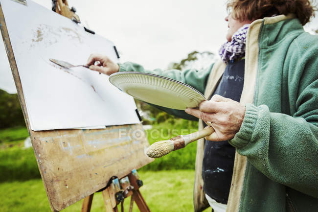 Woman artist working at easel outdoors — Stock Photo