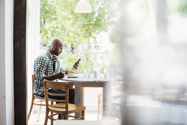 Man sitting in cafe and using phone — Stock Photo