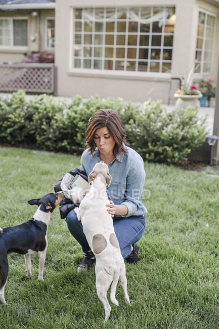 Mulher jogando com dois cães — Fotografia de Stock
