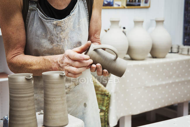 Potter handling a wet clay pot — Stock Photo
