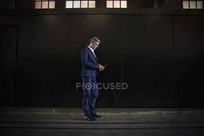Geschäftsmann, stehen im Schatten auf Stadtstraße — Stockfoto