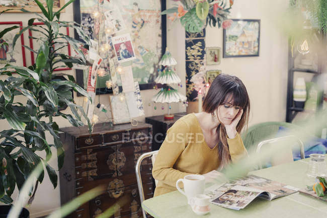 Woman sitting and reading a magazine — Stock Photo