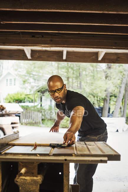 Man working in lumber yard — Stock Photo