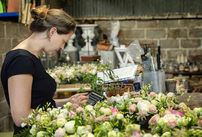 Florist working using digital tablet — Stock Photo