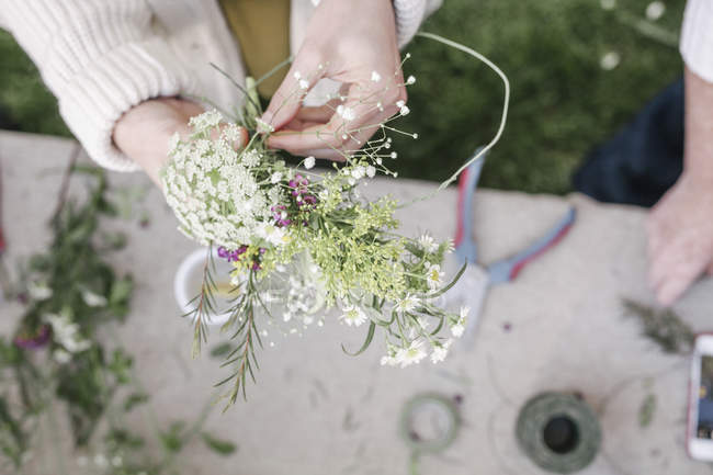 Mulher fazer uma coroa de flores. — Fotografia de Stock