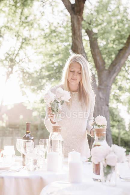 Mulher colocando uma mesa em um jardim — Fotografia de Stock