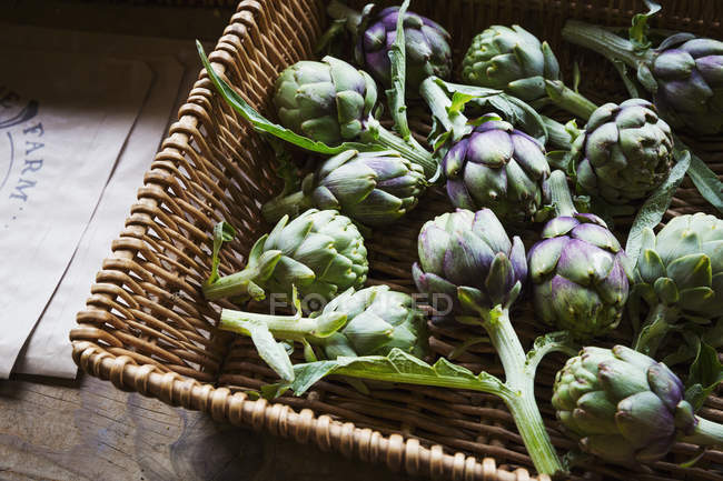 Organic artichokes in basket — Stock Photo