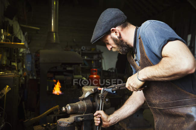 Blacksmith bends a cone of hot metal — Stock Photo