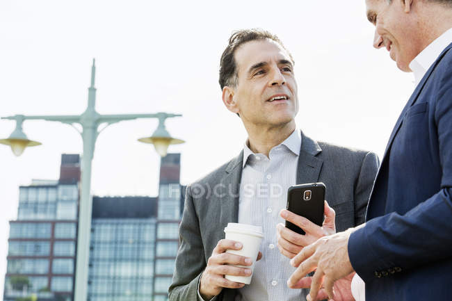 Men talking together leaning on railing — Stock Photo