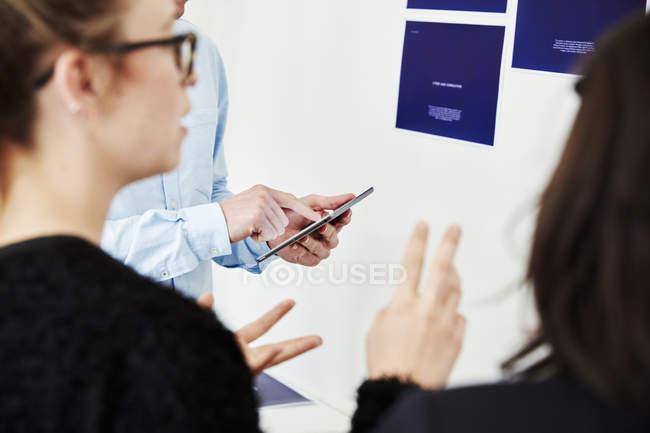 Pessoas ao lado de uma parede coberta de cartazes . — Fotografia de Stock
