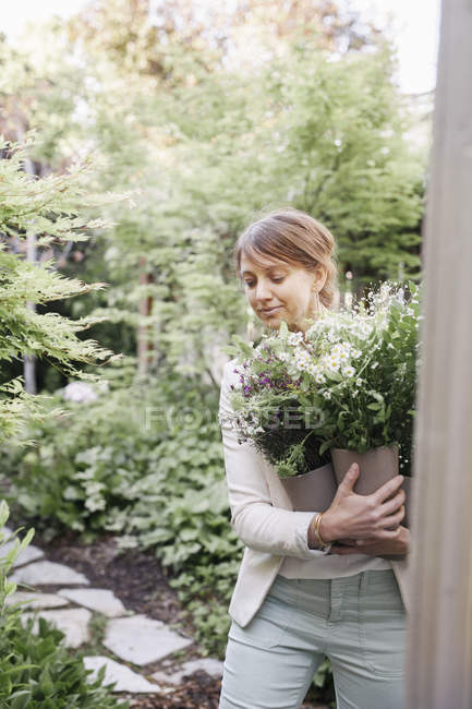 Mulher que carrega um monte de flores brancas. — Fotografia de Stock