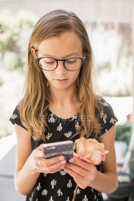 Girl holding cellphone and rose — Stock Photo