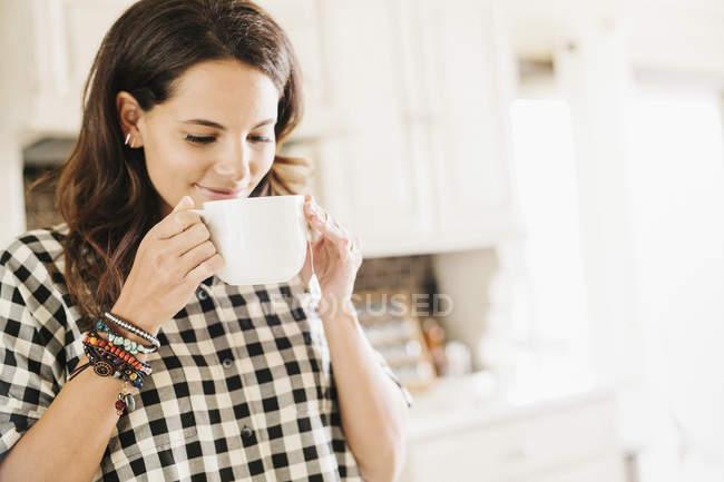 Женщина пьет из кружки. — стоковое фото