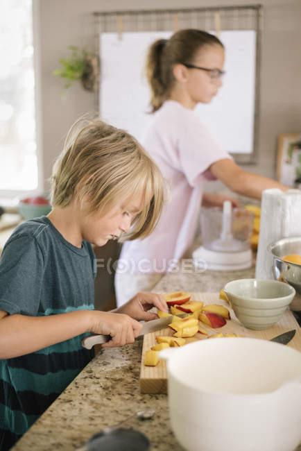 Хлопчик нарізкою фруктів — стокове фото