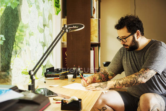 Man with tattoos drawing — Stock Photo