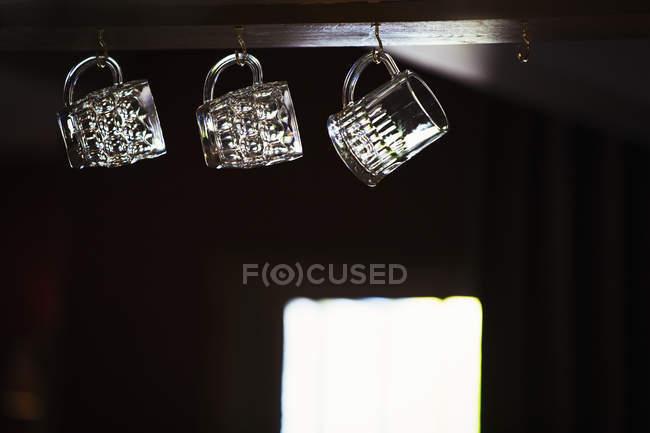 Three beer mugs hanging from hooks — Stock Photo