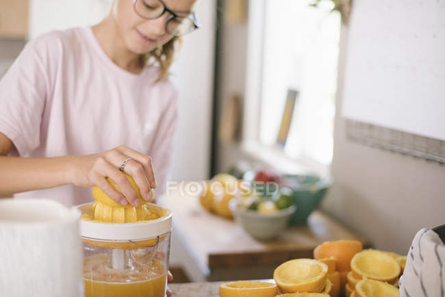 Girl squeezing oranges — Stock Photo