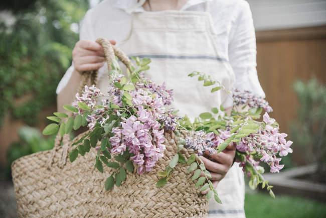 Mulher com cesto de flores cor de rosa. — Fotografia de Stock