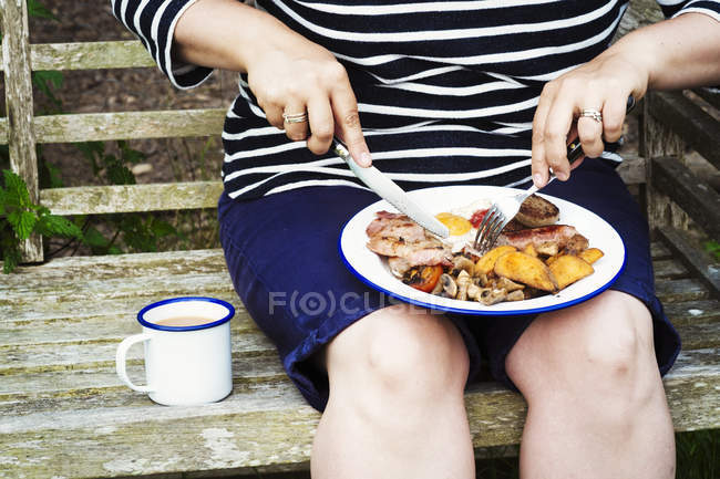 Женщина ест от пластины на скамейке — стоковое фото