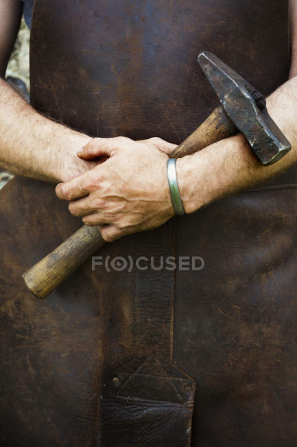 Man in a leather apron holding a hammer — Stock Photo