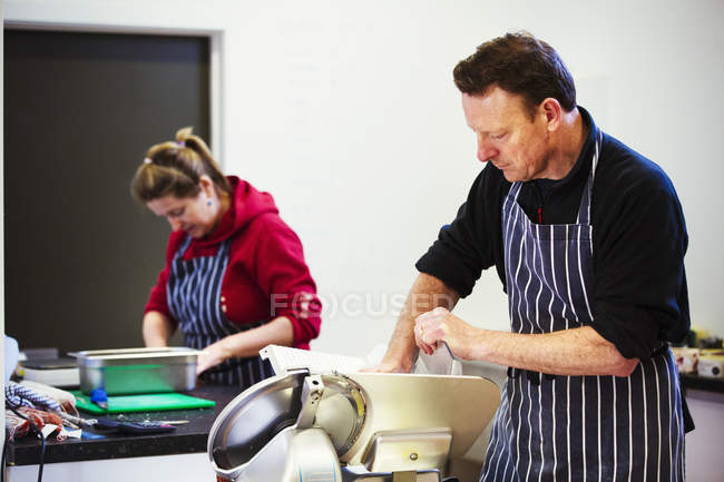 Woman and man working in butchery — Stock Photo