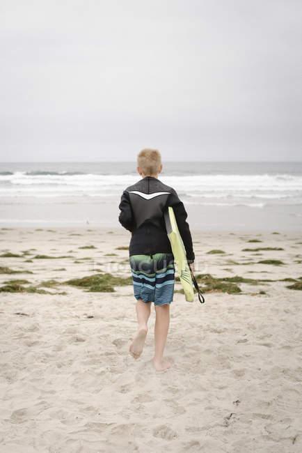 Jungen tragen Bodyboard und zu Fuß ins Meer — Stockfoto