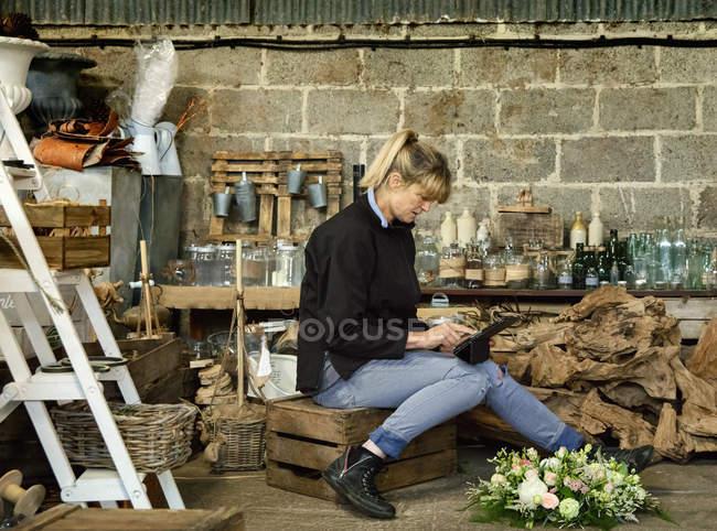 Женщина, сидящая на обрешетке с помощью цифровой планшет — стоковое фото