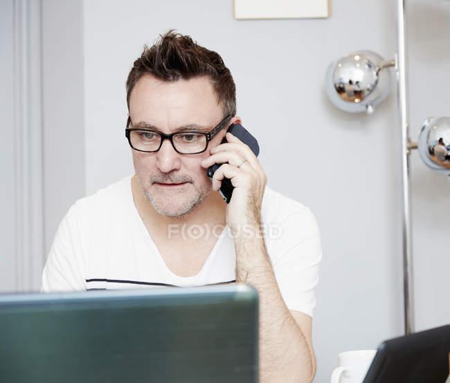 Homem sentado na mesa e falando ao telefone — Fotografia de Stock