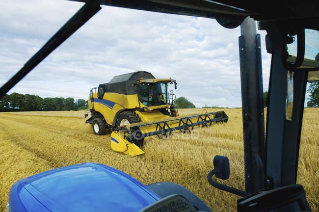 Combine harvester working alongside tractor — Stock Photo