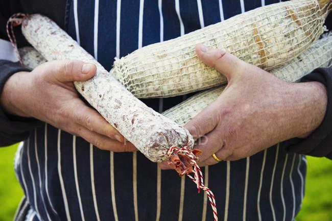 Carnicero con selección de Salamina - foto de stock
