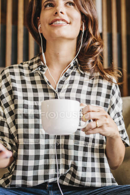 Woman wearing headphones and holding a mug. — Stock Photo